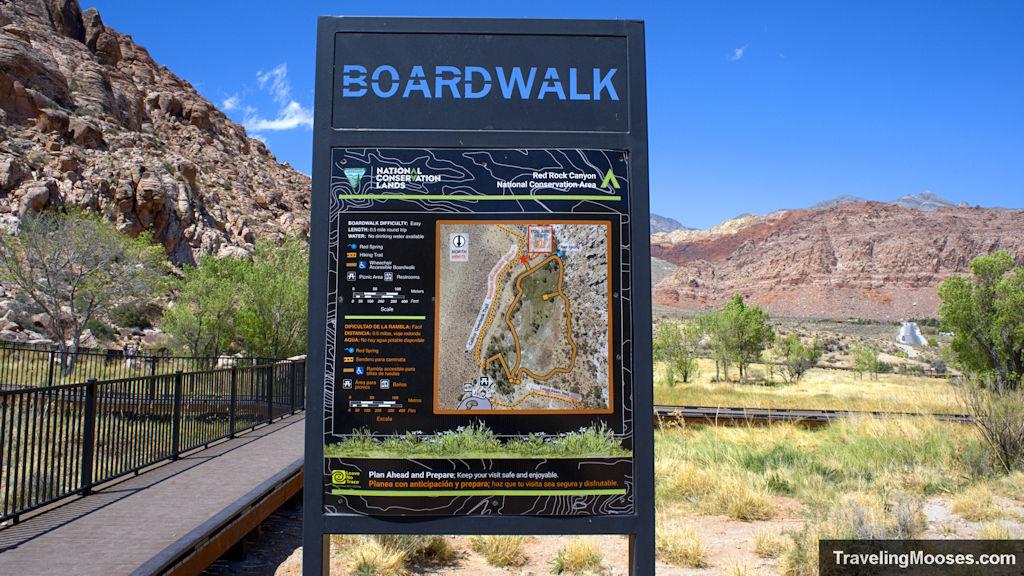 Boardwalk trail sign in red spring meadow