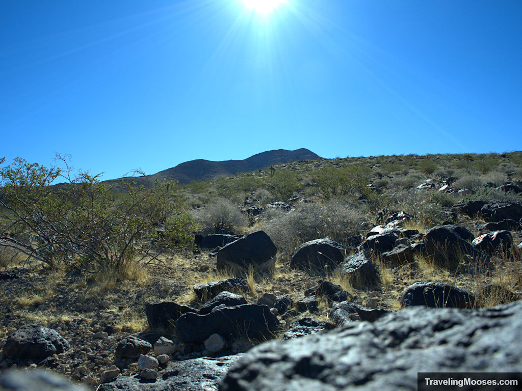 Manganese oxide rocks with black mountain summit in the distance
